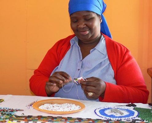 A woman making beaded jewelry at Khayelitsha craftmarket