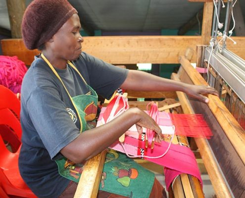 A woman weaving at Philani weaving project